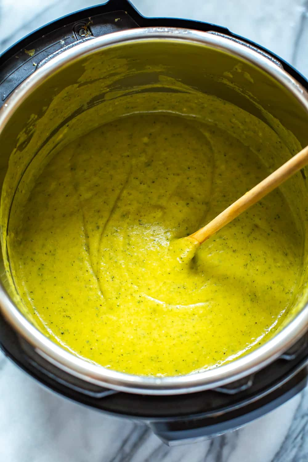 stirring homemade broccoli cheese soup in an Instant Pot