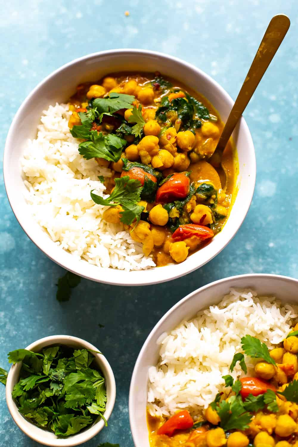 chickpea curry, cherry tomatoes, and leafy greens in a bowl with white rice