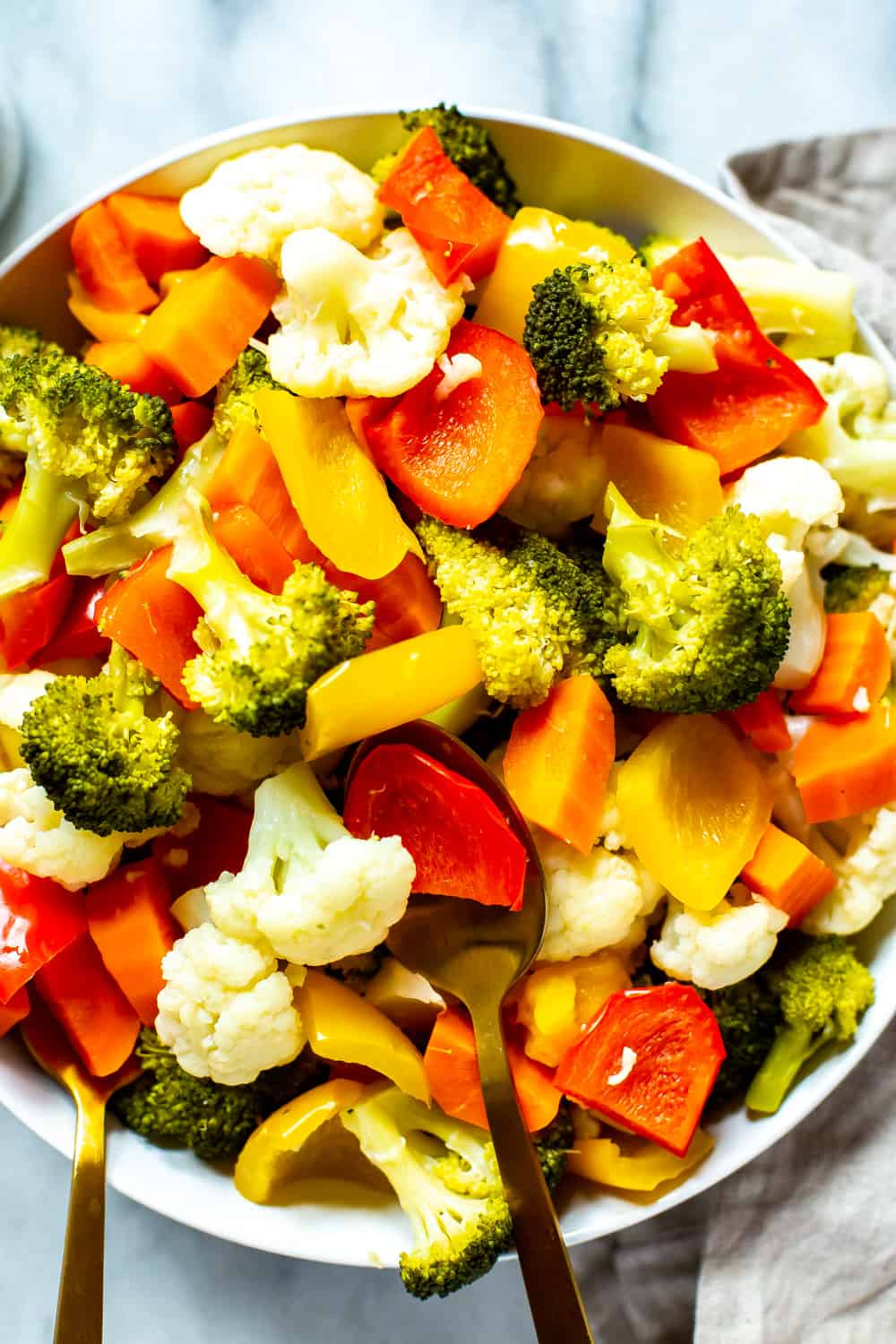 steamed broccoli, cauliflower, and carrots in a large white bowl